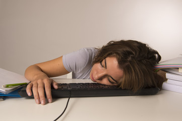 young attractive student girl or working woman sitting at computer desk in stress sleeping tired exhausted and boring