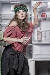 Hippie standing with glass of milk at open fridge door