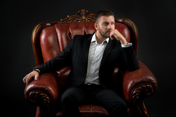Man in formal outfit in leather chair on black background.