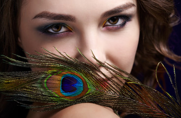 Portrait of beautiful brunette woman on black background and peacock feather
