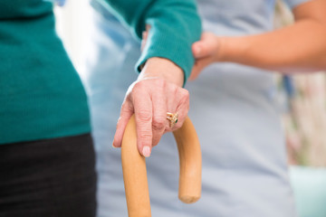 Senior Woman's Hands On Walking Stick With Care Worker In Background