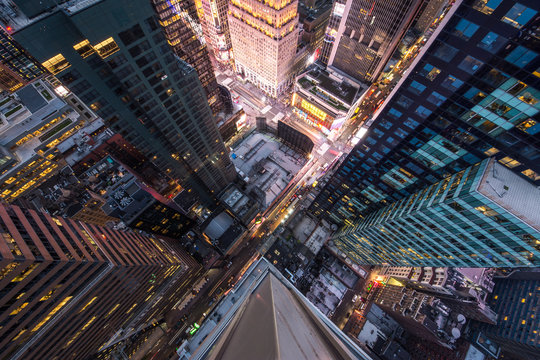 Bird's eye view of Manhattan, looking down at people and yellow taxi cabs going down 5th Avenue.