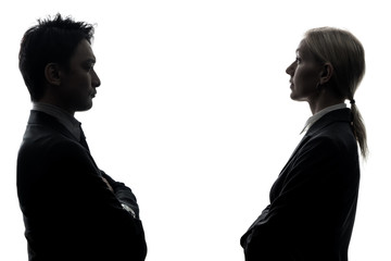 Silhouettes of caucasian businesswoman and asian businessman standing face to face.