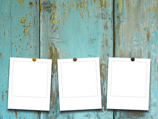 Three blank square photo frames on old weathered aqua wooden boards background