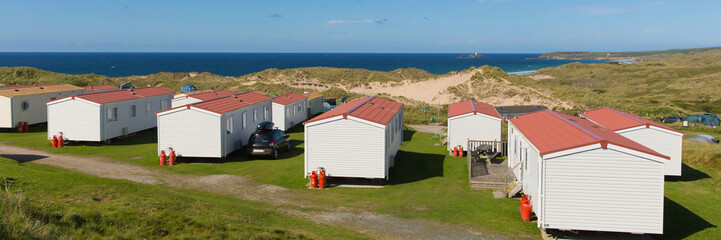 Wall Mural - Static caravans with panoramic view to beautiful Cornish coast in summer with beautiful blue sky