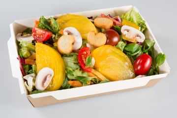 Greek salad in paper carton kraft package isolated on a white background. Salad for take away or food delivery
