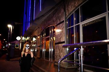 Halloween skull make up girl wear in black at night street of city.