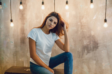 Wall Mural - Sexy woman in a white T-shirt on a gray background with light bulbs. Mock-up.