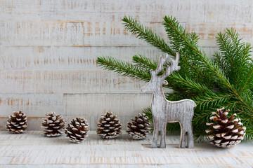 Weihnachten - Holzhintergrund mit Rentier, Tannenzweigen und Tannenzapfen