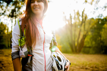 Photo of young athlete with bicycle helmet at autumn forest