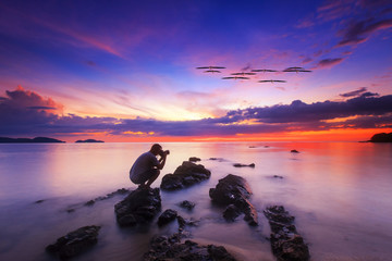 silhouette of photograhper  standing on rock in the sea with sunset sky, long speed exposure,Tarn-khu beach at Trat, Thailand