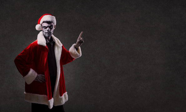 A man in Santa's costume with a makeup skeleton on his face. Christmas. Halloween.