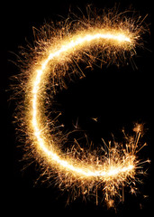 Sparkler firework light alphabet C isolated on black