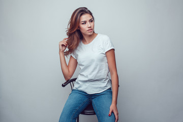 Wall Mural - Sexy woman in a white T-shirt on a gray background. Mock-up.