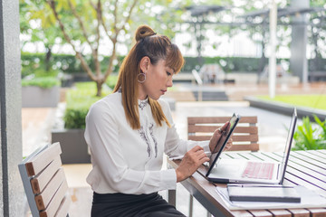 Elegant modern business woman working on tablet screen in an urban environment
