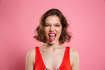 Close-up portrait of funny brunette woman showing tongue, looking at camera
