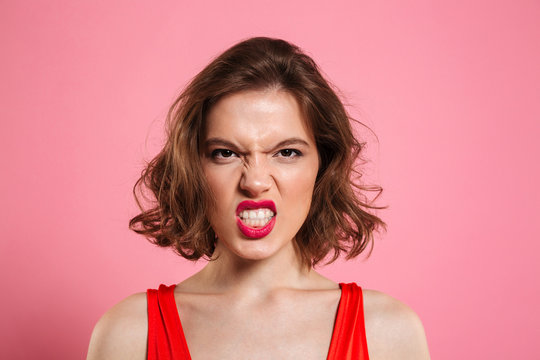 Close-up portrait of angry young woman with red lips looking at camera