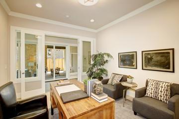 Light home office features a wooden desk