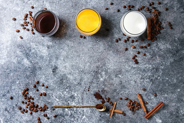 Ingredients for cook spicy pumpkin latte. Glasses with black coffee, pumpkin milk, cream with spices, coffee beans and decorative pumpkins above over gray texture background. Top view, space.
