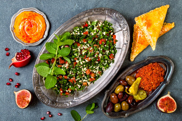 Middle Eastern traditional dinner. Authentic arab cuisine. Tabbouleh, sambusek, muhammara, pumpkin hummus. Top view, flat lay, overhead