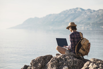 Young woman using laptop computer on a sea. Freelance work concept.People using devices to plan trips, check in to hotels and flights, stay connected to family and office from remote part of the world