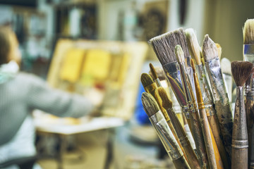 Old stained paintbrushes on the foreground close up and a girl painting a picture on the blurred background. Art lesson in studio.