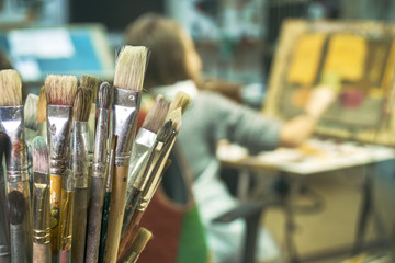 Paintbrushes on the foreground close up and a girl painting a picture on the blurred background. Art lesson in studio.