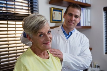 Physiotherapist examining neck of a female patient