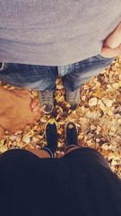 Vista superior de una pareja cogiéndose la mano en otoño