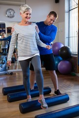 Physiotherapist assisting senior woman in performing exercise on