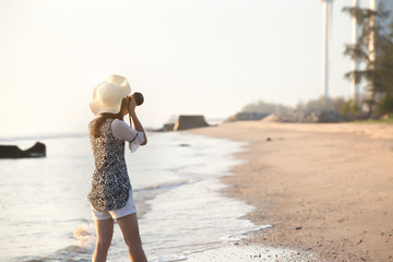 Woman is shooting on the beach with a camera.