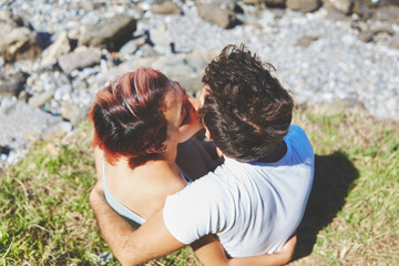 Girl sitting on grass with boyfriend kissing him