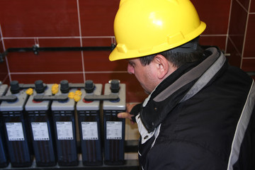 Electrician with yellow helmet check  accumulator