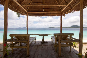 landscape with two bamboo beds in front of the sea in raja ampat archipelago