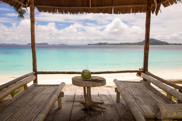 small table with coconut near two bamboo beds in front of the sea in raja ampat archipelago