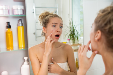 Young beautiful woman surprised to see pimple on skin. Unhappy girl with stunned funny face standing in towel in bathroom, looking in the mirror, pointing to zit