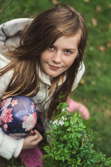 Young girl picking up parsley from her home grown garden.