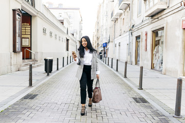 Elegant cheerful woman with phone on street