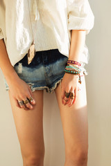 close up of women`s legs in boho style in denim shorts and a white blouse