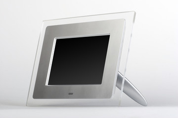 Digital frame with black screen. Transparent glass and silver frame on white background