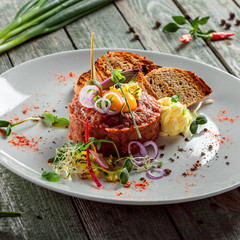 Delicious tartare with toasted bread and salad on a plate. Healthy lunch meal made of raw meat. Classical French cuisine.