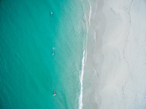 Aerial view of people swimming in turquoise sea