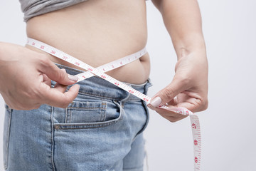 Woman measuring her waistline fat tummy on gray background,obese women,Body part of a fat woman with measuring tape. Beauty ,Health and weight loss concept
