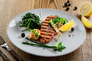 Plate with delicious grilled salmon fish steak and salad on a wooden table. Healthy gourmet food made of fish and vegetables.