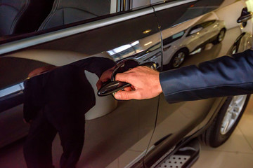 Business man hand holding car doorhandle
