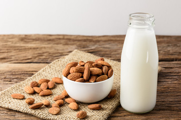 Peeled almonds with bowl and Bottle of almond milk on rustic wooden