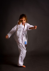 A little girl karate in a white belt, but already received three patches performs kata