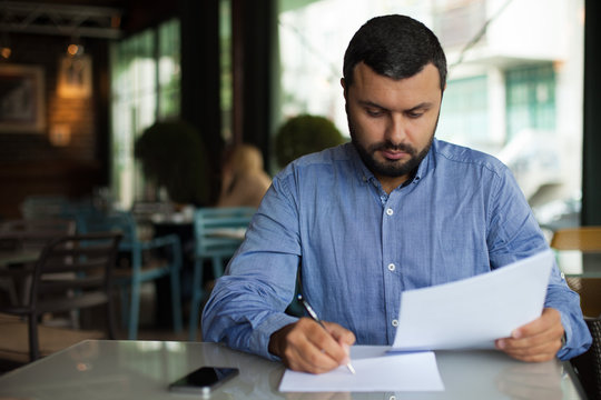 Young businessman writing document