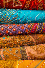 Close up of heap of cloth fabrics at a local market in India, vertical view