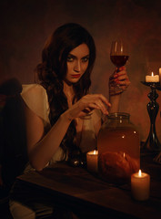 A beautiful, insidious witch drinks wine and guards the heart in a jar. Gothic Photography